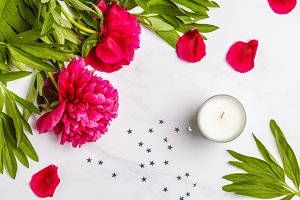 flat lay with a candle and peonies