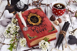 Teacup with magic book and flowers