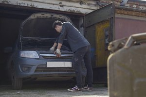Canister stands in front of young man repairs car in garage