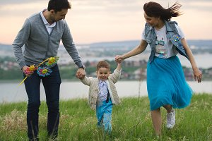 Parents with a baby have fun and walking outdoor