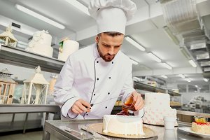 A confectioner with a cake in the bakery