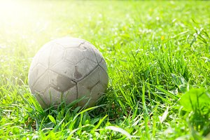 Old soccer ball on the green grass