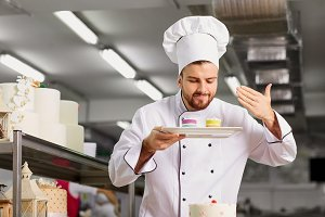 Man confectioner with a cake in his hands in the pastry.