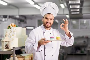 The confectioner is preparing a cake in the kitchen of the pastr