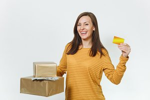 Beautiful caucasian smiling young happy birthday woman in yellow clothes holding credit card, lot of cash money, golden gift boxes with present, celebrating holiday party on white background isolated.
