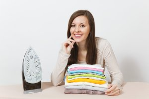 Close up suspicious housewife in light clothes ironing husband checkered shirt, clothing on ironing board with iron. Woman isolated on white background. Housekeeping concept. Copy space advertisement.