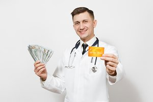 Smiling young doctor man isolated on white background. Male doctor in medical uniform, stethoscope holding bundle of dollars, banknotes cash money, credit card. Healthcare personnel, medicine concept.