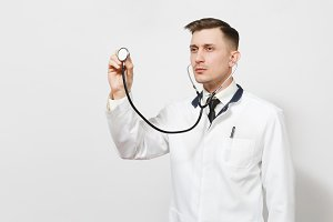 Serious confident experienced handsome young doctor man isolated on white background. Male doctor in medical uniform using and showing stethoscope. Healthcare personnel, health, medicine concept.