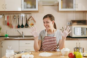 A young beautiful happy woman sitting at a table with flour and going to prepare a Christmas cakes in the kitchen. Cooking home. Prepare food.