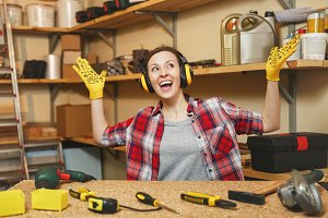 Young woman in plaid shirt, gray T-shirt, noise insulated headphones, yellow gloves spreading hands, working in carpentry workshop at wooden table place with piece of wood, different tools. Copy space