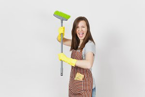 Young crazy housewife in striped apron, yellow gloves isolated on white background. Fun housekeeper woman cleaning maid holding and sweeping with broom. Copy space for advertisement. Advertising area.