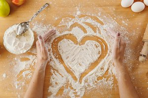 Hand drawn heart in flour on the kitchen table and other ingredients. Top view.