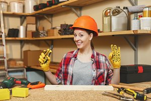 Pretty caucasian young brown-hair woman in plaid shirt, gray T-shirt, yellow gloves, protective helmet working in carpentry workshop at wooden table place with piece of wood, nippers, different tools.