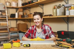 Beautiful smiling caucasian young brown-hair woman in plaid shirt, gray T-shirt, yellow gloves working in carpentry workshop at wooden table place with piece of iron and wood, different tools.