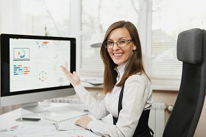 Beautiful smiling brown-hair business woman in suit and glasses sitting at the desk, working at computer with documents in light office, pointing at the modern monitor, looking at the camera