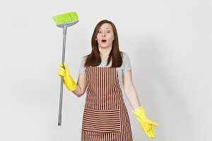 Young shocked housewife in striped apron, yellow gloves isolated on white background. Housekeeper woman cleaning maid holding and sweeping with broom. Copy space for advertisement. Advertising area.