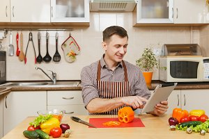 Handsome caucasian young man in an apron, brown shirt sitting at table, looking recipe in tablet, cuting vegetable for salad with knife in light kitchen. Dieting concept. Cooking at home. Prepare food
