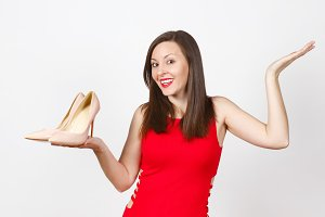Pretty glamour caucasian fashionable young brown-hair woman in red dress holding beige shoes with red sole of her shopping on palm of hand isolated on white background. Copy space for advertisement.