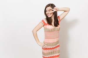 Beautiful young brunette girl in light beige and pink patterned dress smiling, holds hand on waist and shows victory gesture finger near eyes in studio on white background. Concept of good mood