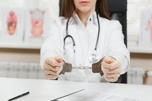 Close up arrested female doctor sitting at desk with medical documents in light office in hospital. Woman in medical gown, stethoscope, hands with handcuffs in consulting room. Medicine, law concept.