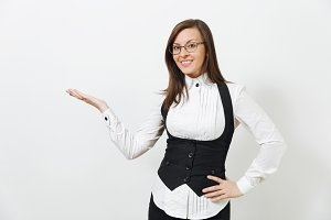 Beautiful caucasian young smiling brown-hair business woman in black suit, white shirt and glasses pointing hand aside isolated on white background. Manager or worker. Copy space for advertisement.