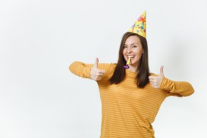 Pretty caucasian young happy woman in yellow clothes and birthday party hat with brown long hair, playing pipe, celebrating holiday, showing thumbs up on white background isolated for advertisement.