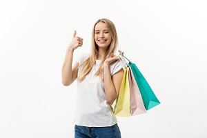 Smiling attractive woman holding shopping bags doing thumb up sign on white background with copyspace