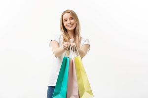 happy attractive caucasian woman offering shopping bags over white background
