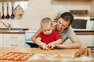 Little kid boy helps mother to cook Christmas ginger biscuit in light kitchen. Happy family mom 30-35 years and child 2-3 roll out dough and cut out cookies at home. Relationship and love concept