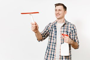 Young housekeeper man in checkered shirt holding squeegee, white blank cleaning spray bottle with cleaner liquid isolated on white background. Male doing house chores. Copy space for advertisement.