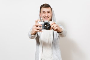 Young handsome excited man student in t-shirt and light sweatshirt with hood with headphones holds retro camera in hands and shows it to camera isolated on white background. Concept of photography