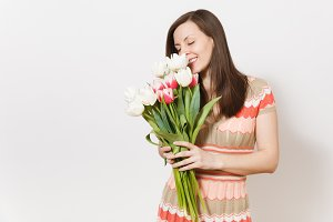 Beautiful young brunette girl in light patterned dress is holding bouquet of white and pink tulips in hands, smiling and sniffing flowers in studio on white background. Concept of holiday, good mood.