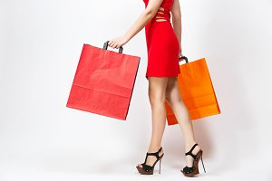 Slender long female legs in black sandals, caucasian woman in red dress holding three multi colored packets with purchases after shopping isolated on white background. Copy space for advertisement.