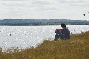 Young sad man sitting on the hill looks into the distance swallows flying over the river