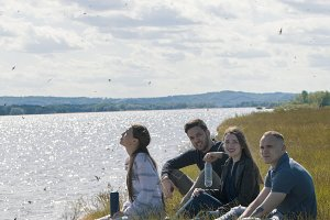 Group of young friends sitting on the on the edge of a hill enjoying recreation outdoors