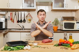 Young man in apron sitting at table showing stop sign with crossed hands, with vegetables, cooking at home meat stake from beef in light kitchen, full of fancy kitchenware. Vegetarianism concept.