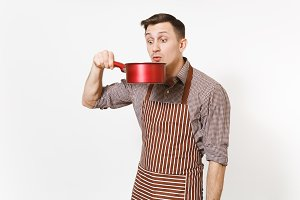 Young fun crazy man chef or waiter in striped brown apron, shirt tasting from red empty stewpan on head isolated on white background. Male housekeeper or houseworker. Kitchenware and cuisine concept.