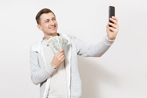 Young handsome smiling man in t-shirt, light sweatshirt with headphones around neck hold bundle of dollars, cash money and pictures himself on phone isolated on white background. Concept of success