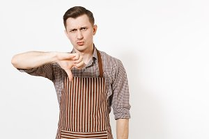 Young sad upset man chef or waiter in striped brown apron, shirt showing thumbs down isolated on white background. Male housekeeper or houseworker looking camera. Domestic worker for advertisement.