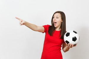 Attractive European young woman, football fan or player in red uniform holding soccer ball, pointing finger aside isolated on white background. Sport, play football, cheer, healthy lifestyle concept.