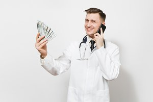 Smiling young doctor man isolated on white background. Male doctor in medical uniform talking on mobile phone, holding bundle of dollars, banknotes, cash money. Healthcare personnel, medicine concept.