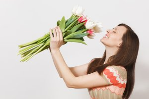 Beautiful young brunette girl in light patterned dress is holding bouquet of white and pink tulips in hands, smiling and sniffing flowers isolated on white background. Concept of holiday, good mood.