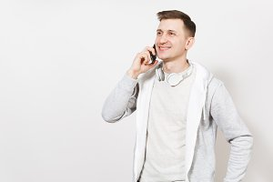 Young handsome smiling man student in t-shirt and light sweatshirt with headphones around neck talks on mobile phone and rejoices isolated on white background. Concept of communication, emotions.
