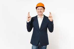 Young businessman in dark suit, protective hardhat keeping fingers crossed and eyes closed and waiting for special moment isolated on white background. Making a wish. Male worker for advertisement.