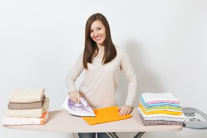 Young attractive housewife in light casual clothes ironing family clothing, towels on ironing board with iron. Woman isolated on white background. Housekeeping concept. Copy space for advertisement.