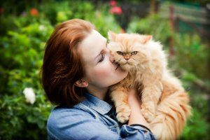 Woman with Persian cat in the garden