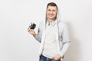 Young handsome smiling student in t-shirt and light sweatshirt with hood with headphones shows retro camera and holds hand in pocket in studio on white background. Concept of photography, hobby