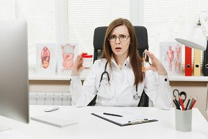 Female doctor sitting at desk, holding bottle with white pills, hourglass, working with medical documents in light office in hospital. Woman in medical gown in consulting room. Time is running out.