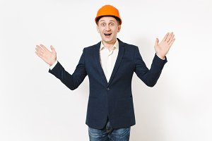Young handsome overjoyed businessman in dark suit, protective construction orange helmet spreading hands with copy space isolated on white background. Male worker for advertisement. Business concept.