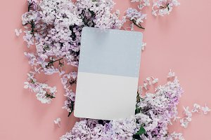 Postcard with lilac flowers flat lay